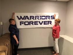 Ruth Illies Licht and Connie Johnson Toavs hanging Warrior Banner